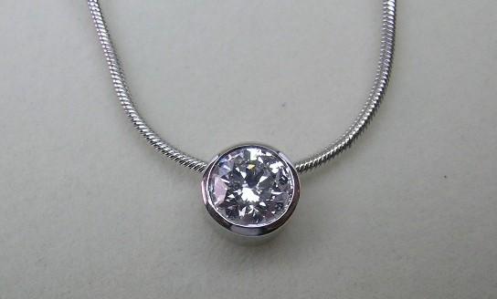 Delicate bezel set round brilliant cut diamond pendant and chain